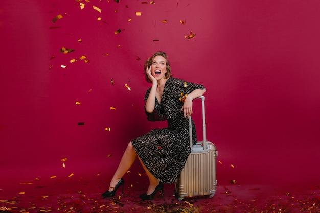 Urocza kobieta w stylowych butach patrząc na konfetti ze zdumieniem
