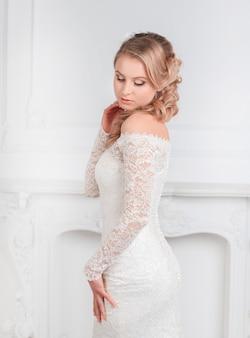 Urocza kobieta w sukni ślubnej pozuje do kamery