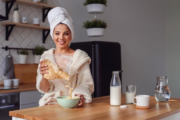 Urocza kobieta w szlafroku i ręczniku na głowie przygotowuje zdrowe śniadanie z płatkami i mlekiem. rano dziewczyna je śniadanie w stylowej, przytulnej kuchni.