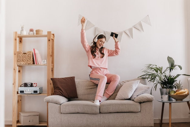 Urocza kobieta w taniec dres, siedząca na kanapie