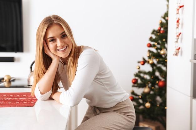 Urocza kobieta w wieku 20 lat uśmiechnięta i siedząca w jasnej kuchni, z choinką
