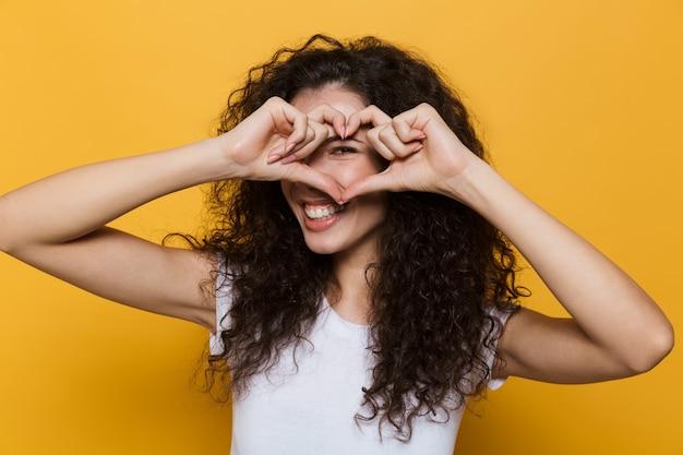 Urocza kobieta w wieku 20 lat z kręconymi włosami, uśmiechnięta i pokazująca kształt serca z palcami izolowanymi na żółto