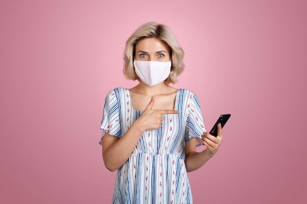 Urocza kobieta wskazuje na ekran swojego telefonu, mając na sobie białą maskę medyczną i letnią niebieską dr...