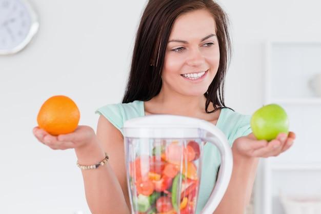 Urocza kobieta z blenderem i owocami