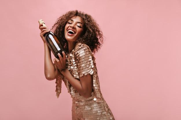 Urocza kobieta z brunetką kręconą fryzurą w błyszczącej stylowej sukience, śmiejąc się i trzymając butelkę z winem na izolowanej ścianie..