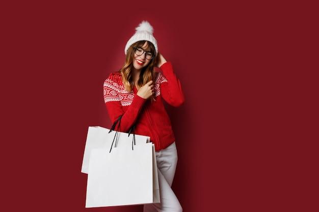Urocza kobieta z falistymi włosami stojący z białymi torbami na zakupy