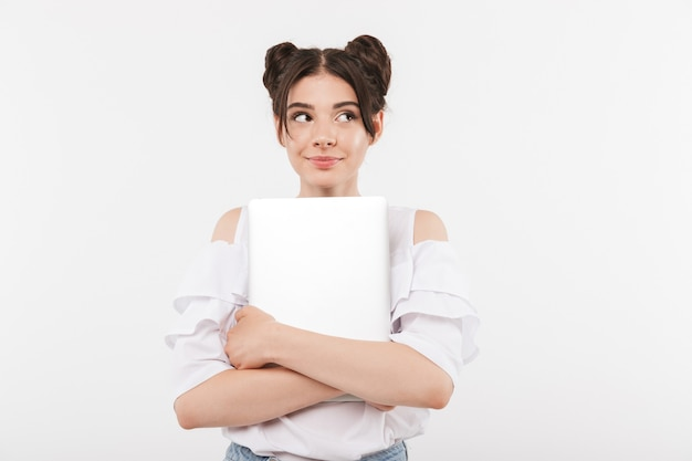 Urocza kobieta z fryzurą double buns uśmiecha się i przytulanie srebrny laptop, na białym tle