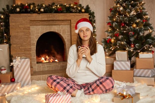 Urocza kobieta z kubkiem herbaty lub kawy przy choince i kominku siedząca ze spokojnym i relaksującym wyrazem twarzy, odpoczywając w domu podczas świąt noworocznych.
