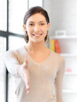 Urocza kobieta z otwartą dłonią gotowa do uścisku dłoni