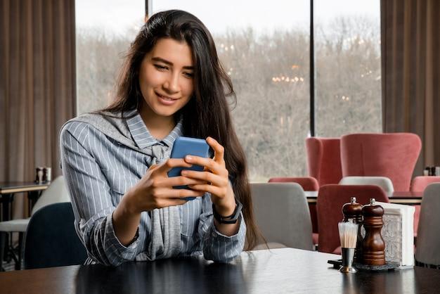 Urocza kobieta z pięknym uśmiechem czytająca dobre wieści na telefonie komórkowym podczas odpoczynku w kawiarni, szczęśliwa kaukaska kobieta oglądająca swoje zdjęcia na telefonie komórkowym, relaksując się w kawiarni w czasie wolnym