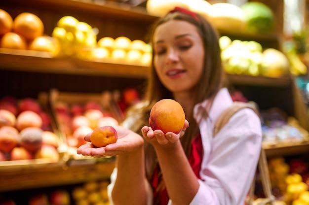 Urocza kobieta z pomarańczą w ręku stojąca w sklepie z owocami