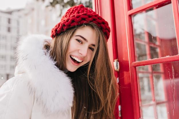 Urocza kobieta z szczęśliwym uśmiechem pozuje blisko czerwonej budki telefonicznej w grudniowy poranek. plenerowy portret cudownej europejskiej damy w zimowej czapce i białym płaszczu.