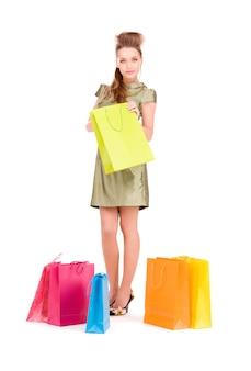 Urocza kobieta z torbami na zakupy na białej ścianie