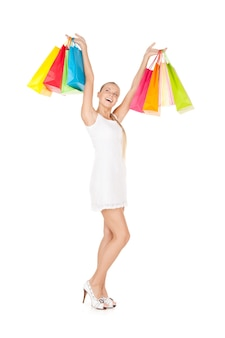 Urocza kobieta z torbami na zakupy na białym?