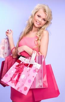 Urocza kobieta z torbami na zakupy na niebiesko