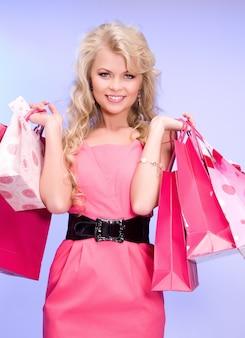 Urocza kobieta z torbami na zakupy nad niebieską ścianą