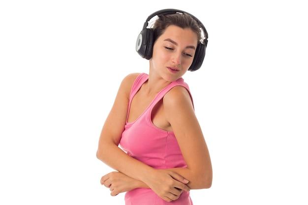 Urocza kobieta ze słuchawkami na białym tle na białej ścianie