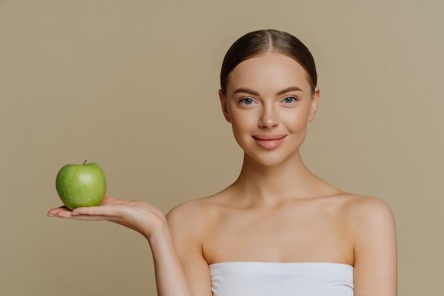 Urocza kobieta ze stojakiem owinięta w ręcznik kąpielowy trzyma zielone jabłko