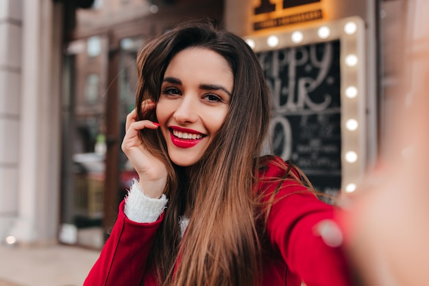 Urocza kobieta ze zmęczonym uśmiechem robi sobie zdjęcie w przestrzeni miasta