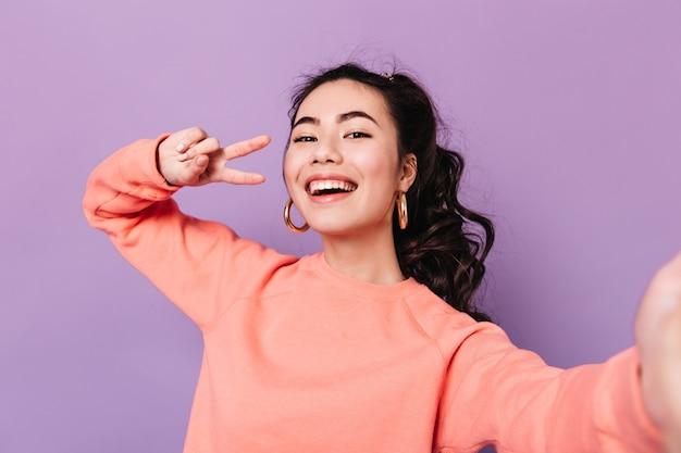 Urocza koreańska kobieta pozuje ze znakiem pokoju. roześmiana azjatycka młoda kobieta przy selfie na fioletowym tle.