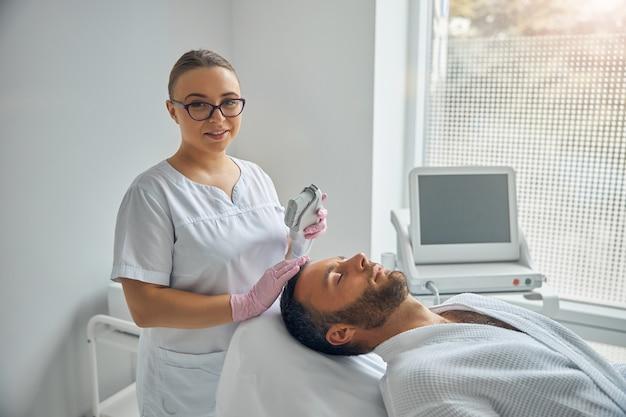 Urocza kosmetolog trzymająca urządzenie laserowe i uśmiechająca się, podczas gdy pacjent leży na tapczanie