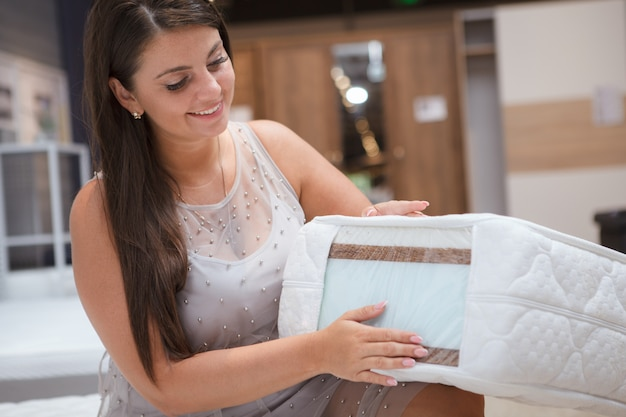 Urocza krągła kobieta kupująca łóżko ortopedyczne i materac