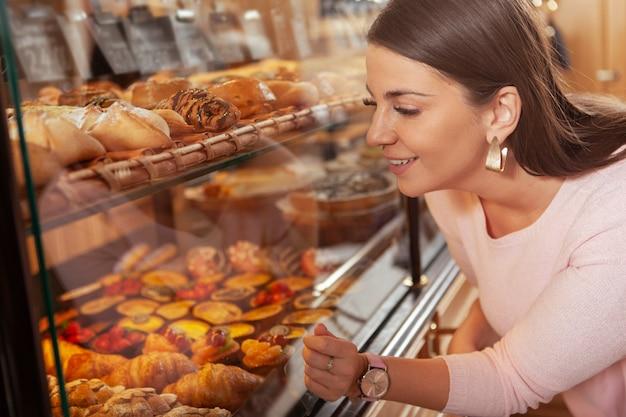 Urocza, krągła kobieta w rozmiarze plus size, która kupuje ciasta