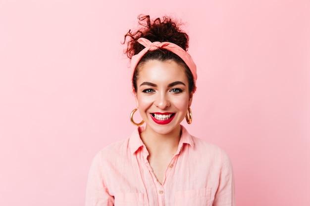 Urocza kręcona brunetka kobieta o niebieskich oczach i czerwonych ustach w różowym stroju pozuje na odosobnionej przestrzeni.