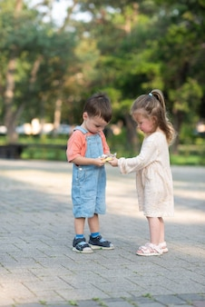 Urocza, kręcona dziewczyna pomaga rozpakować cukierka i traktuje chłopca stojącego z przodu pośrodku parku