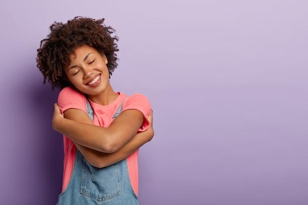 Urocza kręcona kobieta obejmuje się z przyjemnością, czuje komfort, spokój i miłość, przechyla głowę i uśmiecha się pozytywnie, z zamkniętymi oczami, pozuje na fioletowej ścianie, pusta przestrzeń