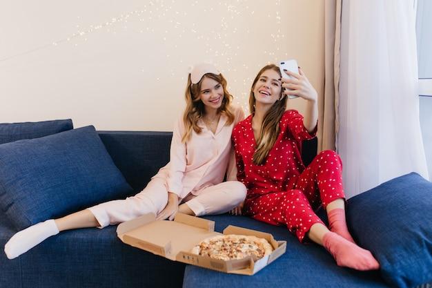 Urocza, kręcona młoda kobieta w białych skarpetkach, uśmiechnięta, podczas gdy jej przyjaciółka robi selfie w domu. wewnątrz zdjęcie dwóch zadowolonych sióstr jedzących pizzę w weekend.