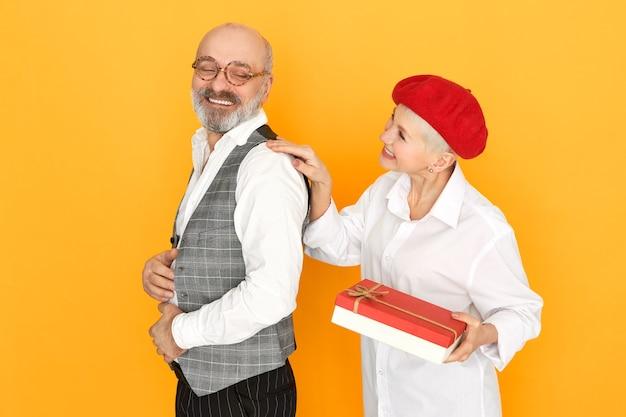 Urocza krótkowłosa kobieta w średnim wieku w czerwonej masce, trzymając pudełko czekolady, dając prezent urodzinowy swojemu przystojnemu mężowi wesołemu