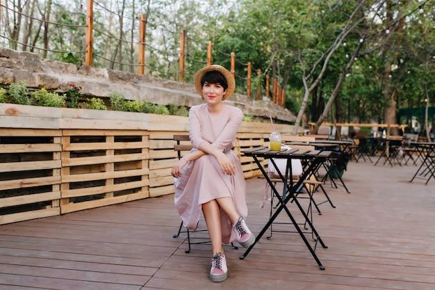Urocza krótkowłosa stylowa dziewczyna odpoczywa w restauracji w parku, ciesząc się weekendem w letni dzień