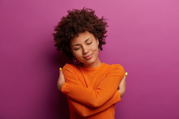 Urocza ładna kobieta obejmuje się, czuje się dobrze, komfortowo i spełniona