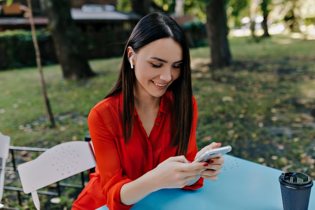 Urocza ładna pani ubrana w czerwoną koszulę, siedząc w kawiarni na świeżym powietrzu ze smartfonem i słuchając muzyki