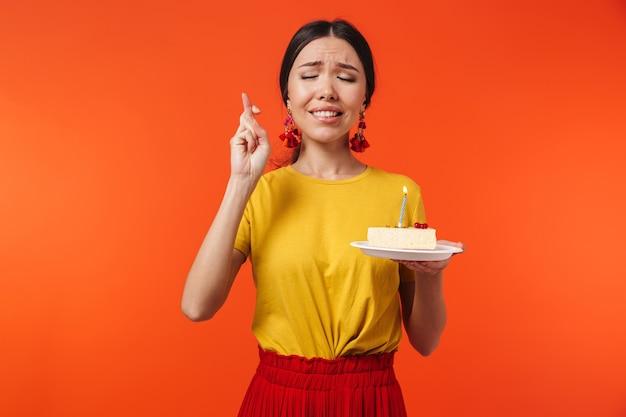 Urocza latynoska lat 20. ubrana w spódnicę, życząc sobie, trzymając tort urodzinowy ze świecą odizolowaną od czerwonej ściany