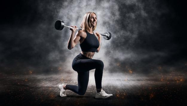 Urocza lekkoatletka pozuje ze sztangą w lekkoatletycznej siłowni. koncepcja fitness i zdrowego stylu życia. różne środki przekazu