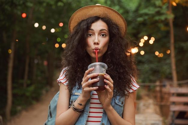 Urocza letnia kobieta w słomkowym kapeluszu, patrząc na ciebie podczas odpoczynku w zielonym parku z kolorowymi lampami pijąc napój z plastikowego kubka