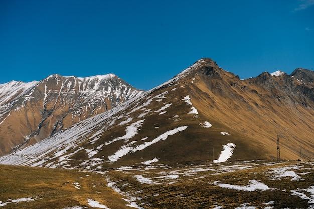 Urocza magiczna przyroda, majestatyczne wysokie góry pokryte białym śniegiem pod błękitnym niebem