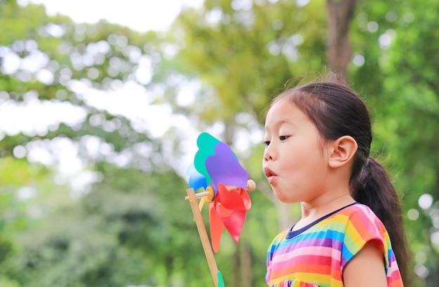 Urocza mała azjatycka dzieciak dziewczyna dmucha silnik wiatrowego w lato ogródzie.
