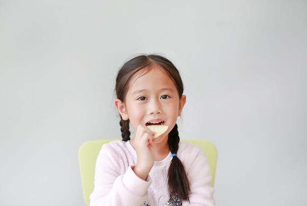 Urocza mała azjatycka dziecko dziewczyna je crispy frytki na bielu.
