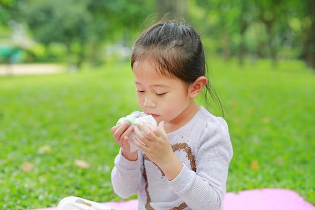 Urocza mała azjatycka dziecko dziewczyna otwiera deserową torbę i wąchać jedzenie w jej rękach przy zielonej trawy ogródem.