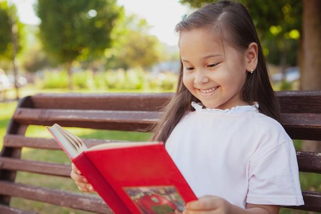 Urocza mała azjatycka dziewczyna przy parkiem w letnim dniu