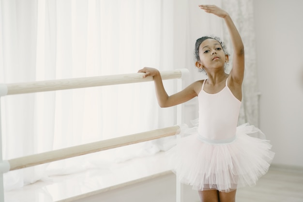 Urocza mała baletnica w różowym stroju baletowym. dziecko w pointe tańczy w pokoju. dziecko w klasie tańca.