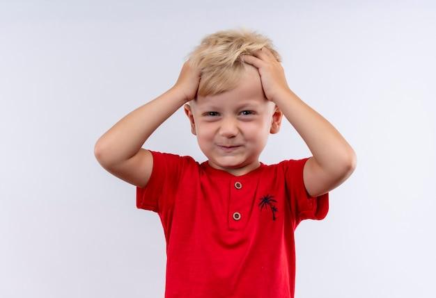 Urocza mała blondynka w czerwonej koszulce trzymając włosy palcami