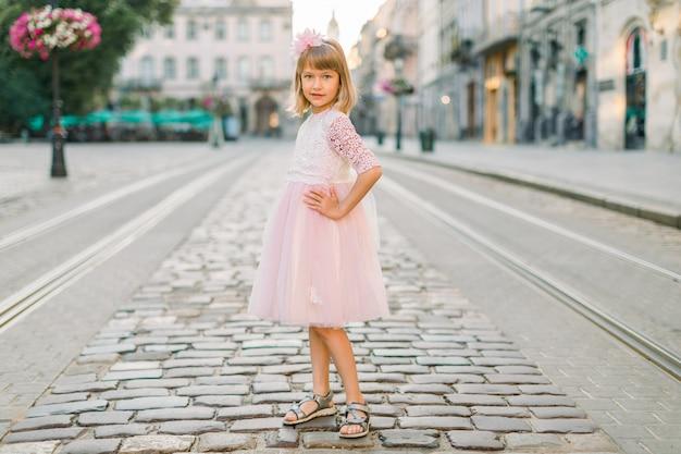 Urocza mała blondynka w różowej sukience w mieście