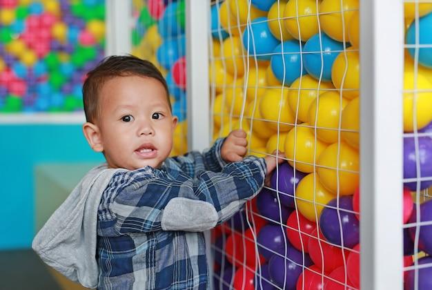 Urocza mała chłopiec bawić się kolorową plastikową piłkę w klatce z przyglądającą kamerą.