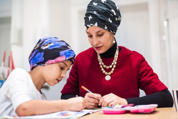 Urocza mała córka 6-7 lat ucząca się pisania z młodą mamą korepetytorką