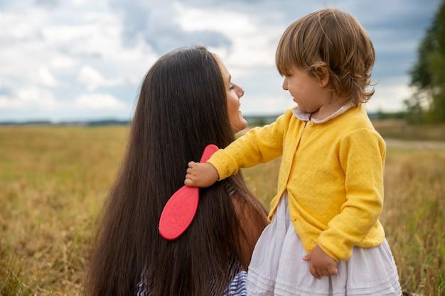Urocza mała dziewczynka bawi się czesaniem włosów swojej mamy na zewnątrz słoneczny dzień miłość matki i córki