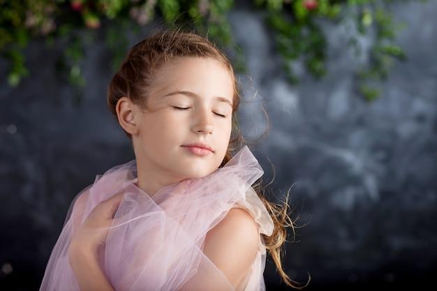 Urocza mała dziewczynka bawi się lekkim materiałem na tle kwiatów. portret miłej dziewczynki. tańcząca mała dziewczynka.